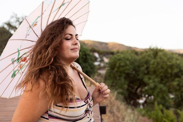 Вид сбоку женщины на открытом воздухе с зонтиком