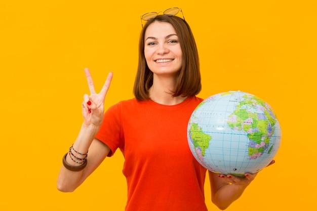 地球を押しながらピースサインを作るスマイリー女性