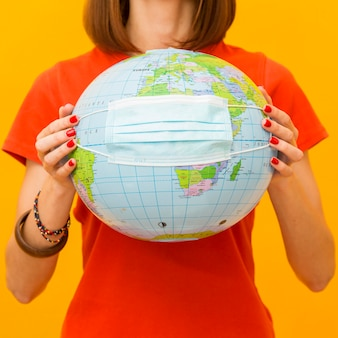 Вид спереди женщина держит глобус с медицинской маской