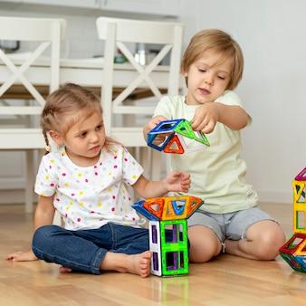 Маленькие дети дома играют с игрушками