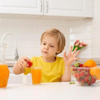 自宅で小さな男の子がジュースを飲む