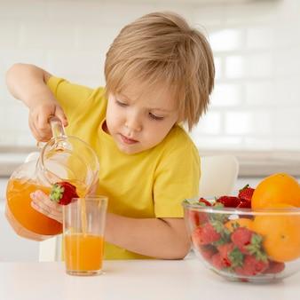 Мальчик наливает сок