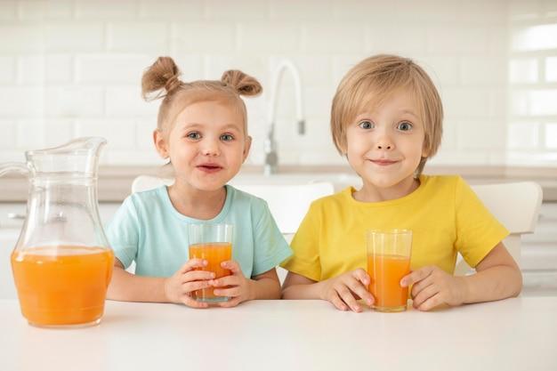 Дети пьют сок дома