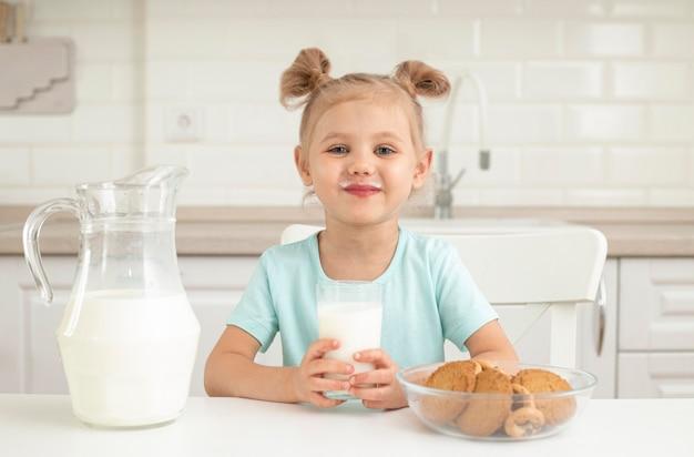 Девушка пьет молоко с печеньем