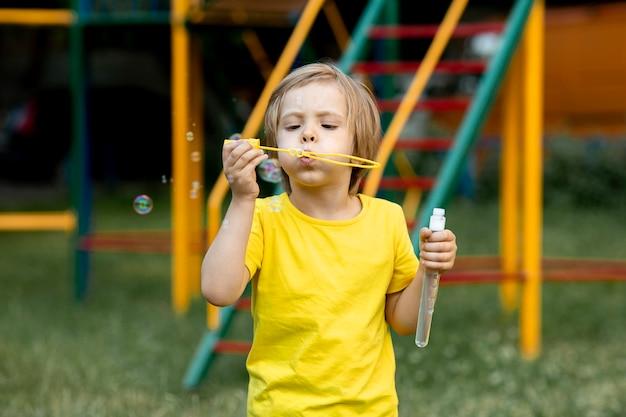 Мальчик играет с мыльными пузырями на открытом воздухе