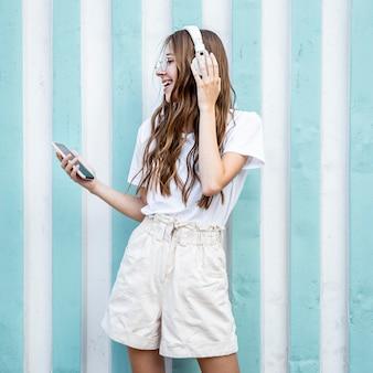 Вид сбоку девушка с наушниками и мобильным