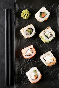 Вид сверху тарелка со свежими суши на столе