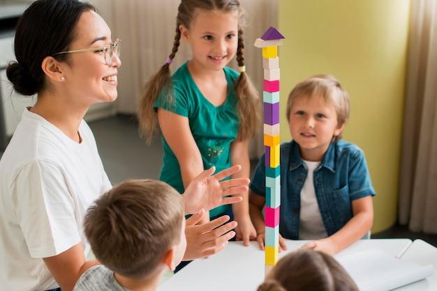カラフルなタワーで遊ぶ方法を子供たちに教える女性