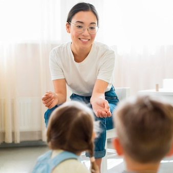 Воспитатель детского сада что-то объясняет своим ученикам