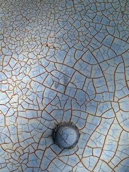 さびた金属壁にひびの入った塗料