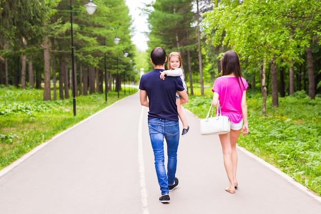 Отец, дочь и мать ходьбе на открытом воздухе. счастливая семья.