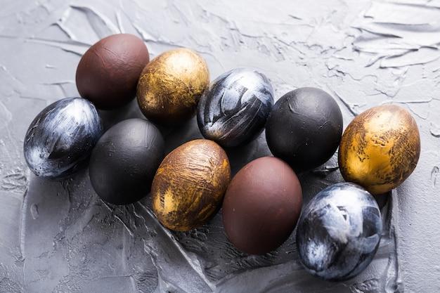 Праздники, традиции и концепция пасхи - темные стильные пасхальные яйца на сером фоне.