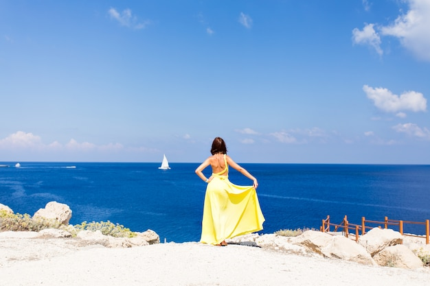 Молодая брюнетка женщина в летнее желтое платье, стоя на пляже и глядя на море.
