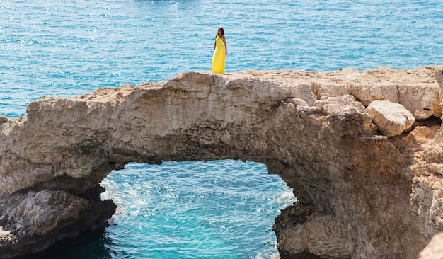 Молодая брюнетка женщина в летнее желтое платье, глядя на море.