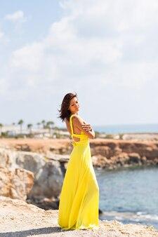 ビーチで黄色のドレスで美しい女性。