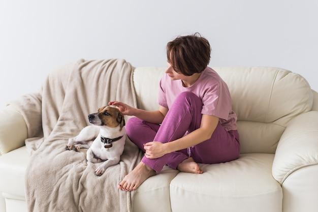彼女のかわいい犬と自宅で若い美しい女性。検疫、隔離、コロナウイルスの世界的流行。家にいる。