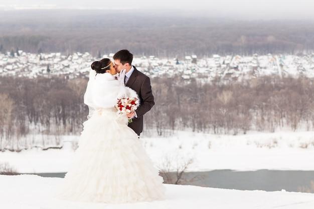 冬の結婚式。美しい若いカップルの新郎新婦