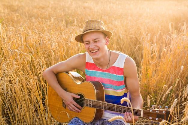 屋外でアコースティックギターを弾く男