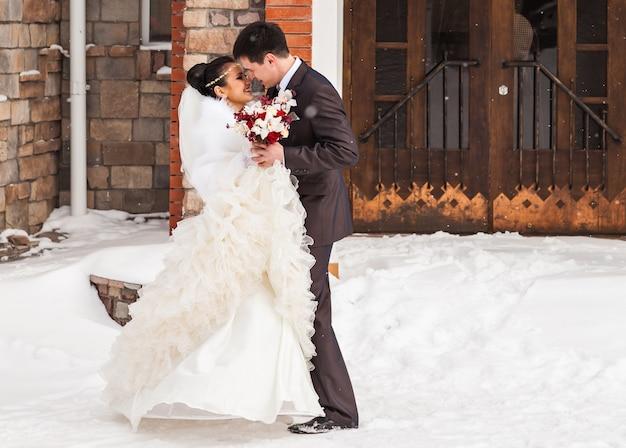 冬の結婚式の日にロマンチックなキス幸せな新郎新婦