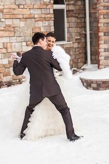 冬のブライダルの日に愛するカップルを踊る新郎新婦の結婚式。幸せのひとときをお楽しみください。