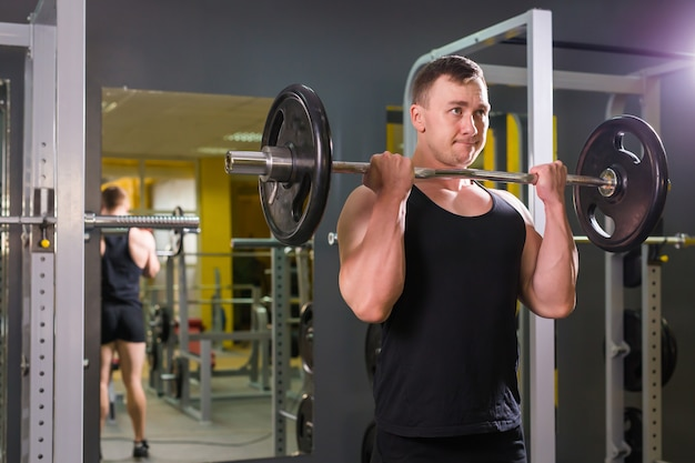 強くてハンサムな男がジムでバーベルの重量を持ち上げる