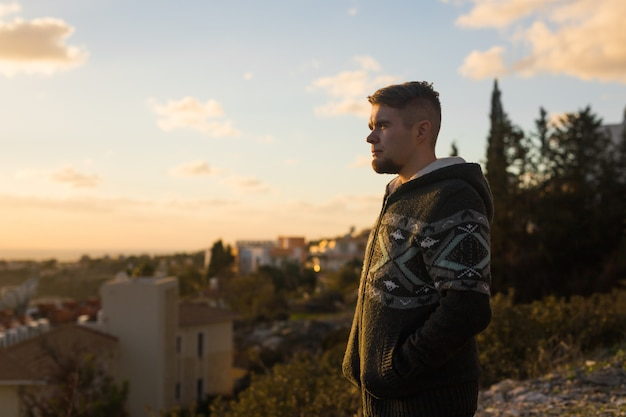 Одинокий молодой человек стоит на горе и смотрит вдаль