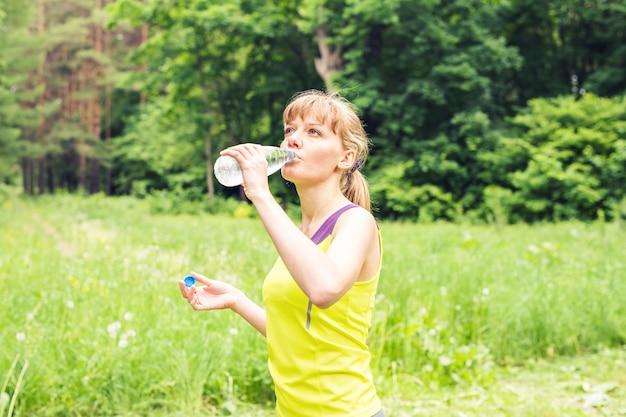 Молодая красивая женщина подходит пить воду после ее тренировки