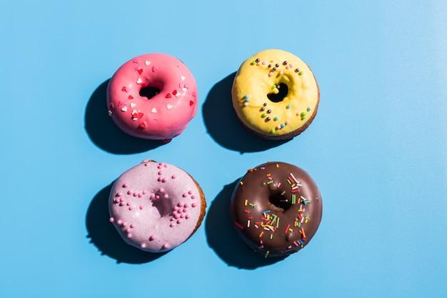 Модный солнечный свет. летние пончики на светло-голубом бирюзовом фоне. минимальная летняя концепция. стиль поп-арт. пончик