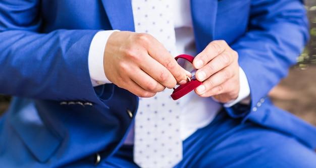 Мужская рука держит обручальное кольцо