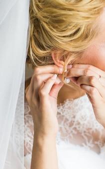 Красивая шикарная невеста надевает роскошные серьги