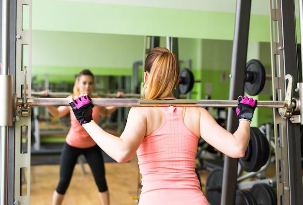 美しくて強い女性はバーベルでスクワットをすることによって彼女のトレーニングルーチンに集中しました