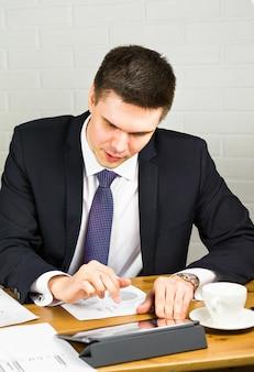 Красивый бизнесмен работает с ноутбуком в офисе