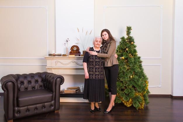 母と娘は笑顔で立ち、カメラのためにポーズをとり、クリスマスツリーに対してお互いをハグします。