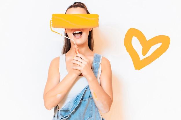 Счастливая женщина прячет лицо малярным валиком. оранжевое сердце на стене. концепция ремонта