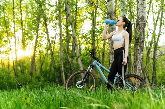 夕日に公園で自転車に乗っている間若い素敵な女性はシェーカーから水を飲む