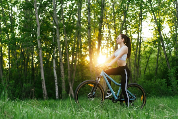 若い素敵な女性が日没で公園で自転車に乗る