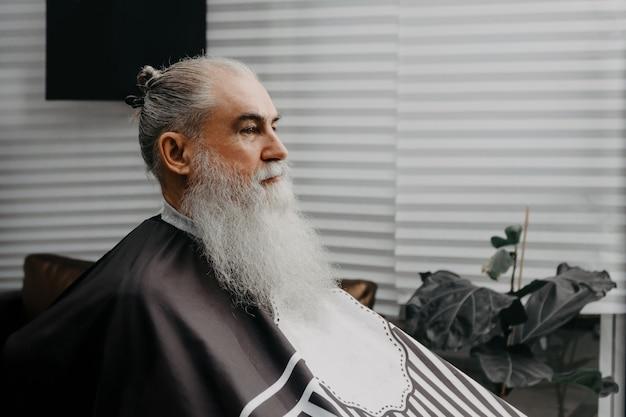 サロンで待っている高齢者のひげを生やした男