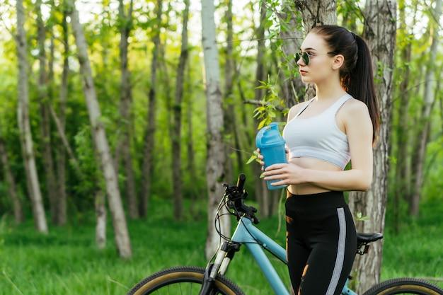 青いシェーカーを持つ若い素敵な女性が公園で自転車に乗る