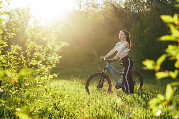 素敵な少女は日没で公園で自転車に乗る