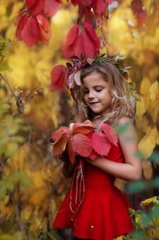 秋の森の少女は葉の花束を見てください。