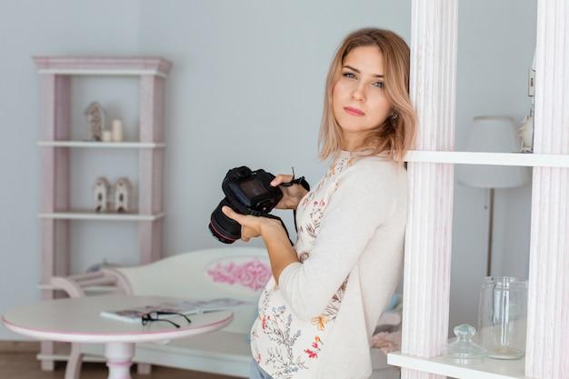 手にカメラを持つ若い女性