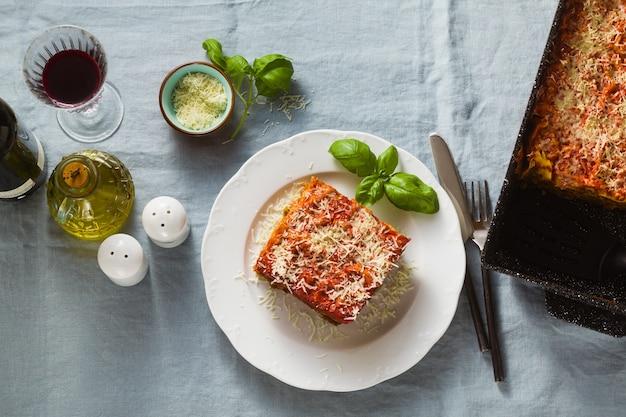 Веганская лазанья с чечевицей и зеленым горошком в противне на столе с голубой льняной скатертью. и красное вино в бокалах