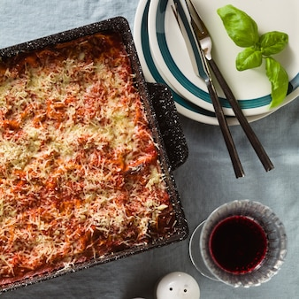 レンズ豆とグリーンピースのビーガンラザニアと青いリネンのテーブルクロスのテーブルの天板。グラスの赤ワイン