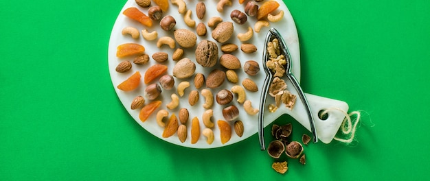 Баннер различных видов сухофруктов и орехов на мраморной разделочной доске на зеленом фоне