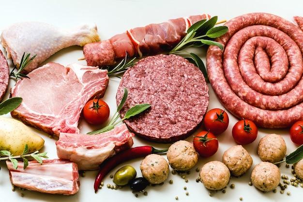 Различные виды сырого мяса: куриные бедра, свиные и говяжьи гамбургеры, ребрышки и шашлыки, фрикадельки из индейки, готовые к приготовлению с картофелем, острым перцем, маслинами и маслинами и ароматическими травами