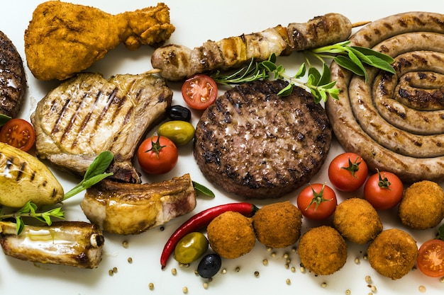 Мясо барбекю с различными видами мяса: говяжьи гамбургеры, свиные ребрышки, фрикадельки из индейки, куриные бедра в панировке с картофелем и помидорами, специями и ароматными травами. летнее меню