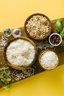 オリーブの木から作られた木の板にさまざまな種類の米。バジルの葉とオリーブオイル。ヘルシー家庭料理