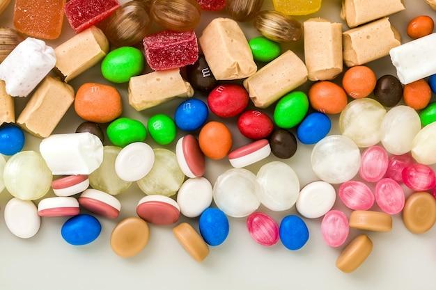 色とりどりのキャラメルのお菓子がテーブルの背景に散在しています。砂糖製品。着色されたお菓子