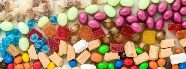 色とりどりのキャラメルのお菓子のバナーがテーブルの背景に散在しています。砂糖製品。着色されたお菓子