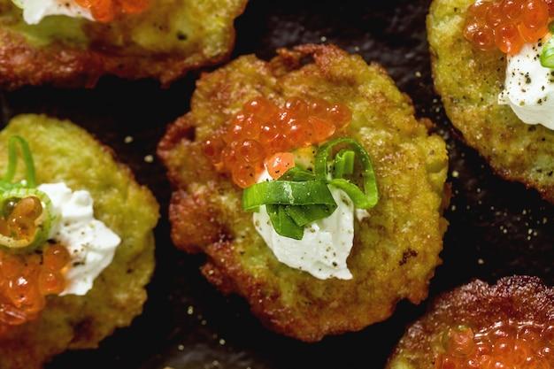 ロシアの伝統的なジャガイモのパンケーキ、赤キャビア、ネギ、サワークリームを白ワインとレモンのトレイに添えて